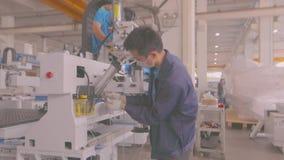 Profesionales jovenes que trabajan en el montaje de la máquina moderna del CNC almacen de video