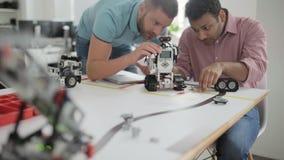 Profesionales jovenes serios que acumulan el robot junto