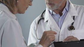Profesionales que discuten qué tratamiento el hospitalizado del método para aplicarse, medicina almacen de video