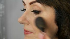 Profesjonalista uzupełnia artysty robi makeup pięknej w średnim wieku dorosłej kobiety z dużymi niebieskimi oczami i malował strz zbiory