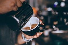 Profesjonalisty Barista dolewanie dekatyzował mleko Robi kawowej latte sztuce w kawiarni fotografia stock