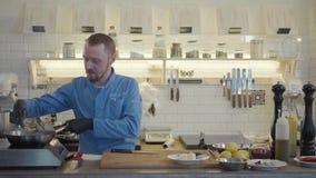 Profesjonalisty kucharz w czarnych gumowych rękawiczkach przygotowywa jedzenie w restauracyjnej kuchni Mężczyzna sprawdza z smażą zbiory