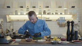 Profesjonalisty kucharz w czarnych gumowych rękawiczkach przygotowywa warzywa dla piec na grillu, ciie zucchini z dużym nożem w zbiory wideo