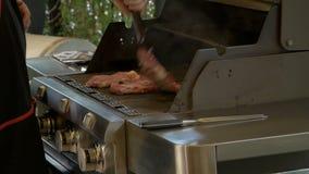 Profesjonalisty kucharza uses metalu tongs obracać mięsnych stki które gotują na benzynowym grillu Kulinarny jedzenie w na wolnym zbiory wideo