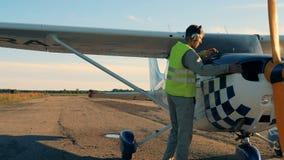 Profesjonalisty pilot przychodzi jego samolot i sprawdza poziom benzyna zdjęcie wideo