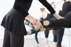 Profesor Adjusting Foot Positions del ballet de bailarinas Foto de archivo libre de regalías