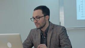 Profesor alegre que trabaja en el ordenador portátil en clase de la educación Imagen de archivo libre de regalías
