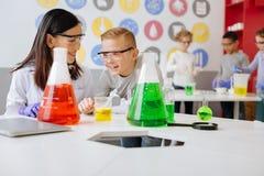 Profesor alegre y estudiante de la química que hablan del experimento y de la risa imagen de archivo