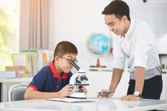 Profesor asiático que se amplía al estudiante en clase de Biología con el microsc Fotos de archivo