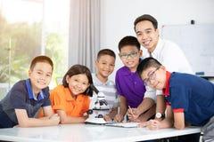Profesor asiático que se amplía al estudiante en clase de Biología con el microsc Fotografía de archivo libre de regalías