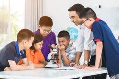 Profesor asiático que se amplía al estudiante en clase de Biología con el microsc Fotografía de archivo
