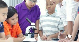 Profesor asiático que se amplía al estudiante en clase de Biología con el microscopio almacen de metraje de vídeo