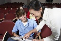Profesor Assisting Male Student en sala de clase Imagen de archivo libre de regalías