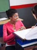 Profesor Assisting Student While que se agacha en el escritorio Foto de archivo