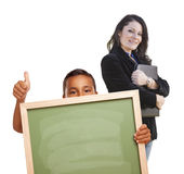 Profesor Behind Boy con el tablero de tiza en blanco que da los pulgares para arriba imagen de archivo