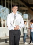 Profesor With Book Standing en campus universitario Foto de archivo