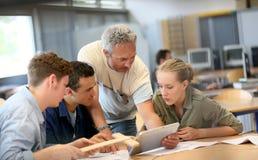 Profesor con el grupo de estudiantes de la carpintería durante clase Foto de archivo