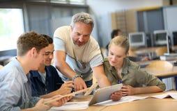 Profesor con el grupo de estudiantes en la escuela Foto de archivo libre de regalías