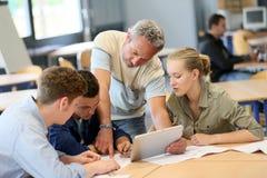 Profesor con el grupo de estudiantes en la tableta Imagenes de archivo