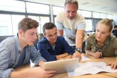 Profesor con el grupo de estudiantes en la tableta digital Foto de archivo libre de regalías