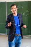 Profesor con el indicador delante de una clase de escuela Fotos de archivo