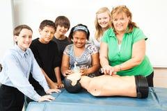 Profesor con la clase y el maniquí del CPR Fotografía de archivo