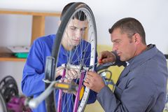 Profesor con los estudiantes en los mecánicos que trabajan en la bici Imágenes de archivo libres de regalías