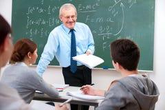 Profesor con los estudiantes en sala de clase Imagenes de archivo