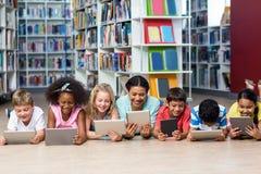 Profesor con los estudiantes que usan la tableta digital Foto de archivo libre de regalías