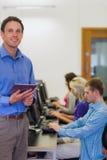 Profesor con los estudiantes que usan los ordenadores en sala de ordenadores Imagen de archivo