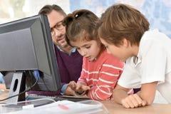 Profesor con los niños en la clase computacional Foto de archivo libre de regalías