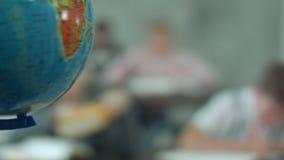 Profesor con los niños en la clase de la geografía que mira el globo almacen de metraje de vídeo
