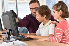 Profesor con los niños que trabajan en el ordenador Imagen de archivo