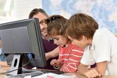 Profesor con los niños que trabajan en el ordenador Foto de archivo libre de regalías