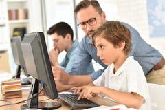 Profesor con los niños que usan el ordenador Imágenes de archivo libres de regalías