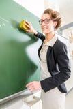 Profesor con una esponja delante de una clase de escuela Fotos de archivo libres de regalías