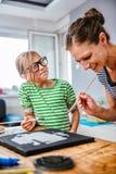 Profesor de arte que ayuda a un estudiante con la pintura Imágenes de archivo libres de regalías