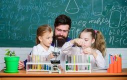 Profesor de escuela de la biolog?a Trabajo barbudo del profesor del hombre con el microscopio y los tubos de ensayo en sala de cl imágenes de archivo libres de regalías