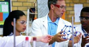 Profesor de escuela que ayuda a alumnos en el modelo 4k de la molécula almacen de metraje de vídeo