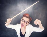 Profesor de griterío enojado con el indicador en fondo de la pizarra imagenes de archivo