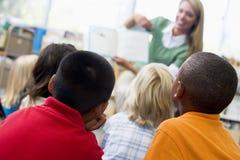 Profesor de jardín de la infancia que lee a los niños