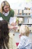 Profesor de jardín de la infancia que muestra la planta de semillero a los niños Imagen de archivo libre de regalías