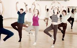 Profesor de la danza que muestra estirando la posición a los adolescentes Imagen de archivo libre de regalías
