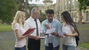 Profesor de la geografía que discute resultados de la prueba pasada con el grupo de estudiantes almacen de video