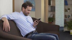 Profesor de la geografía que se sienta en el sofá y que enrolla en el smartphone, tecnologías almacen de metraje de vídeo