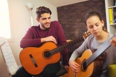Profesor de la guitarra que enseña a la niña fotografía de archivo