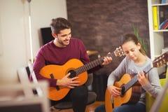 Profesor de la guitarra que enseña a la niña imagen de archivo