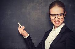 Profesor de la mujer de negocios con vidrios y un traje con tiza   en a Imagenes de archivo