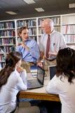 Profesor de la universidad con los estudiantes que hablan en biblioteca Fotos de archivo
