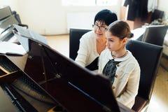 Profesor de música con el alumno en el piano de la lección Fotos de archivo libres de regalías